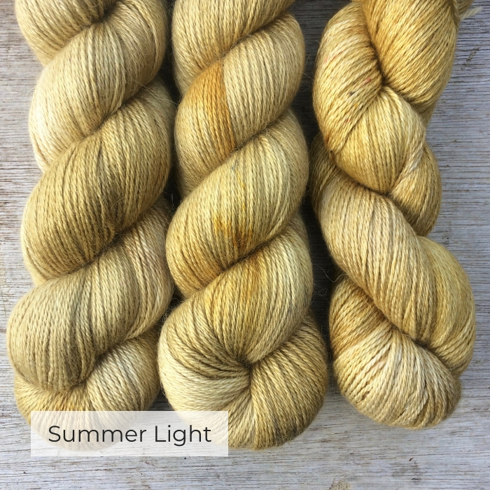 Three skeins of yarn in mellow yellow and cream, lightly speckled in brown, rust and mustard