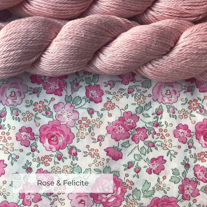 Two skeins of pale pink cotton yarn on a white fabric printed with pink roses