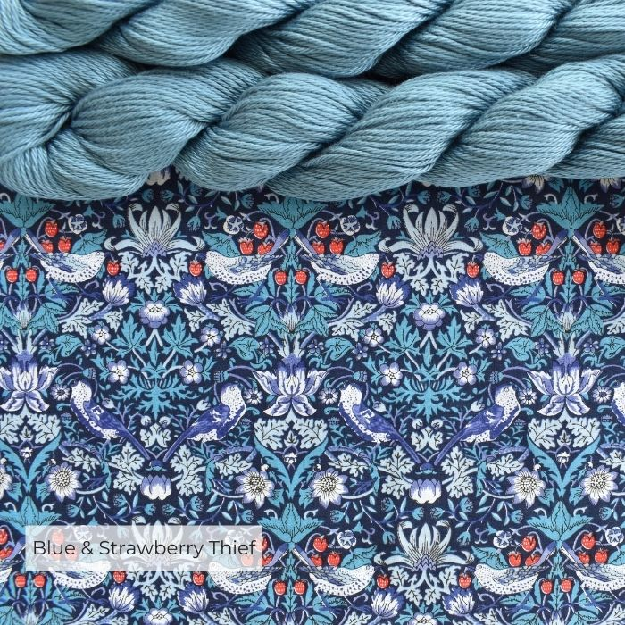 Two skeins of pale blue cotton yarn laying at the top of a piece of William Morris' strawberry thief fabric in Tana Lawn