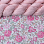 A piece of white fabric printed with roses in shades of pink and two skeins of soft pink cotton yarn
