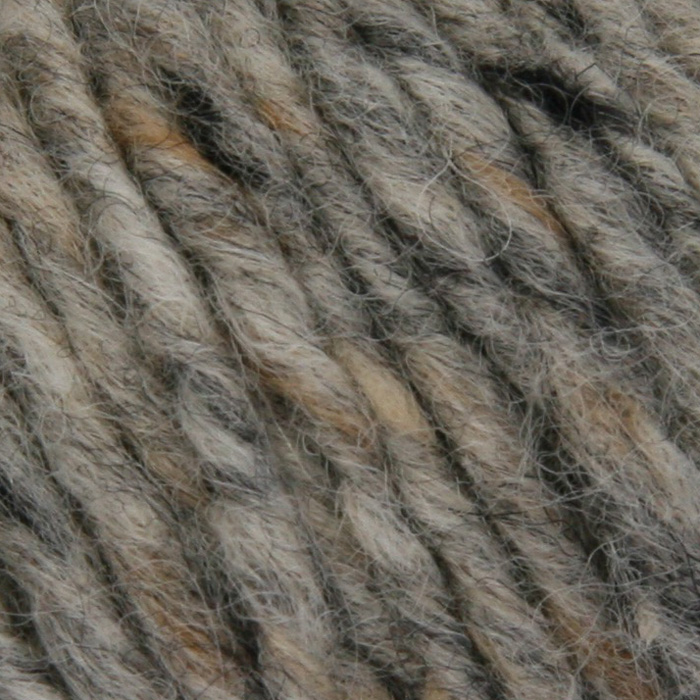 A close up of a light grey tweedy yarn with flecks of black and buff