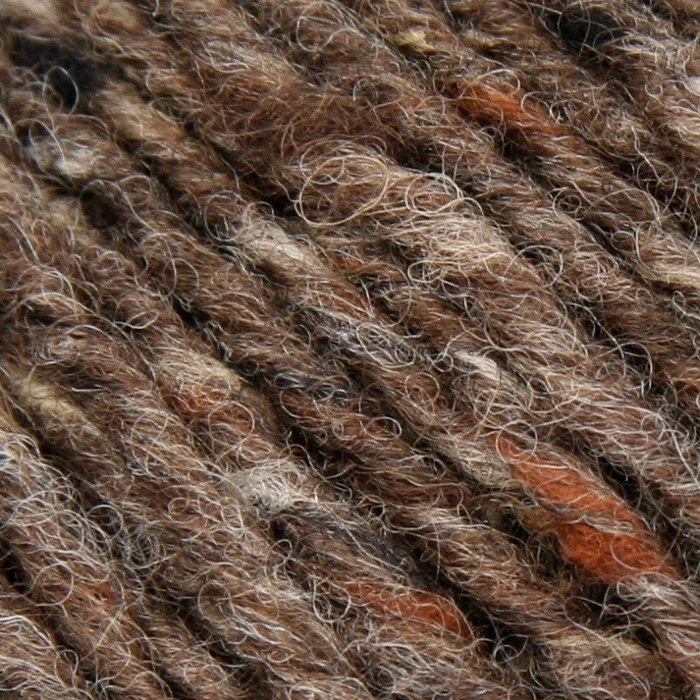 A close up of a rich brown tweedy yarn with decks of grey and tan