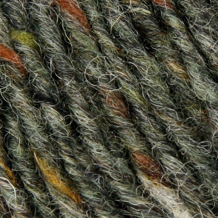 A close up of tweedy yarn, grey-brown with specks of orange, green and tan
