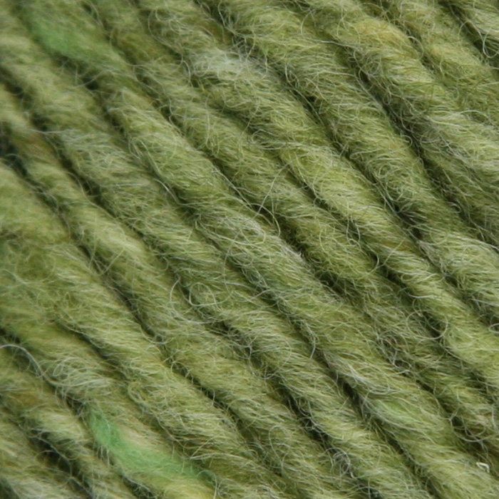 A close up of a soft moss green tweedy yarn flecked with bright green and moss