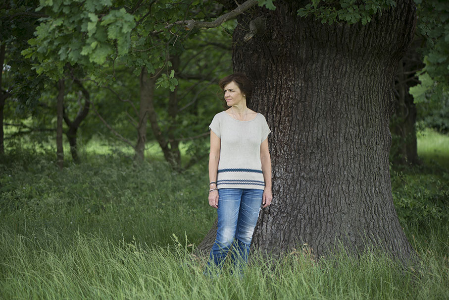 A woman standing under a tree wearing a linen knitted jumper