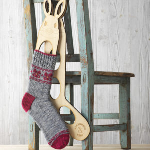 Grey and red hand knit sock with Fair Isle pattern blocked on rabbit shaped shock blockers hanging on the back of a chair