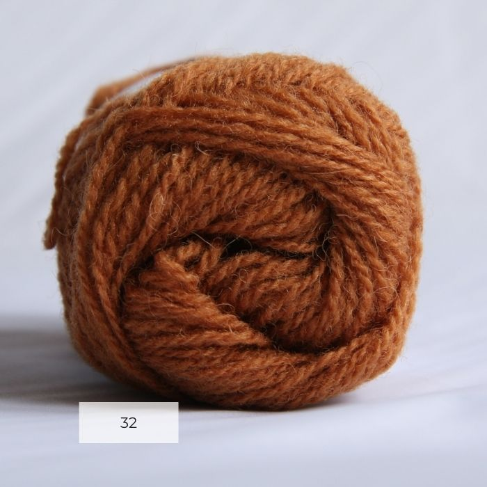The end of a single ball of shetland wool in an amber colour