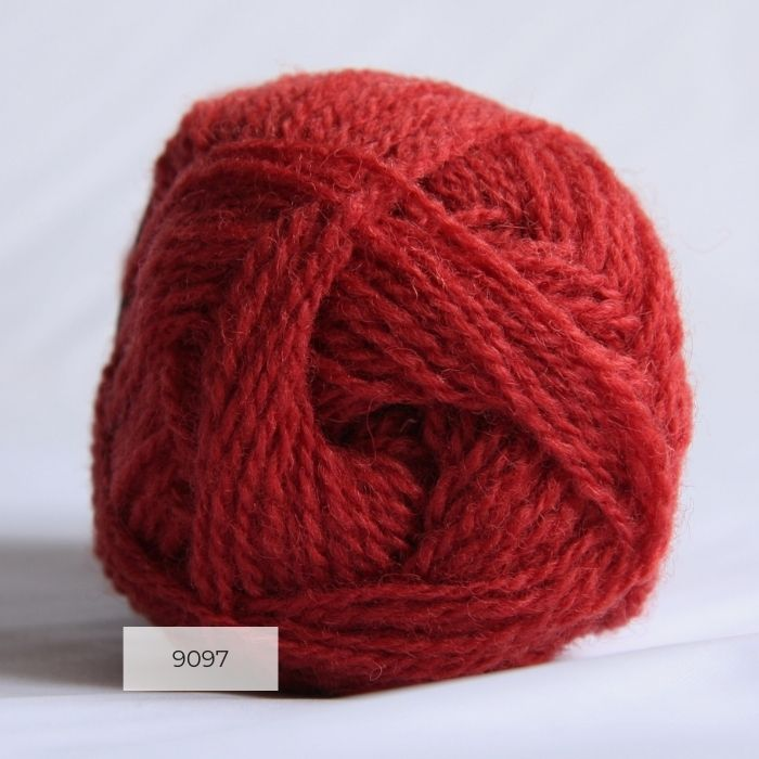 The end of a single ball of shetland wool in a bright coral colour