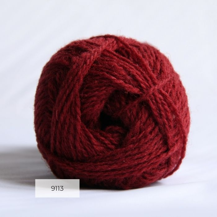 The end of a single ball of shetland wool in a deep red colour