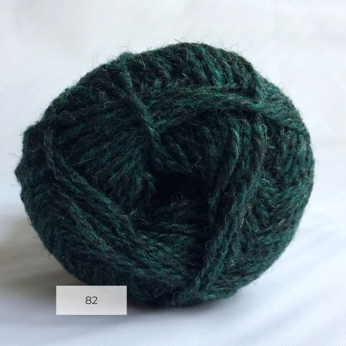 The end of a single ball of shetland wool in dark blue green colour