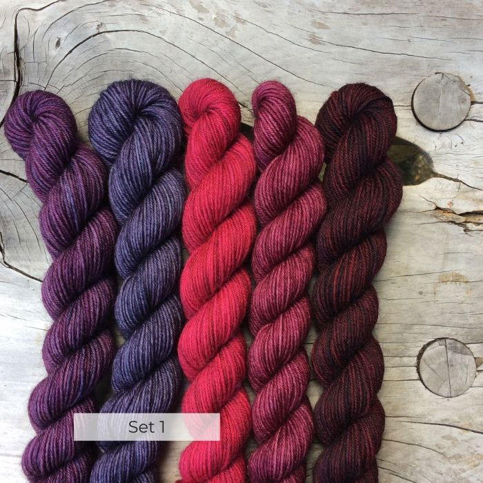 Five small skeins of British BFL wool in berry and pink shades on a wood background