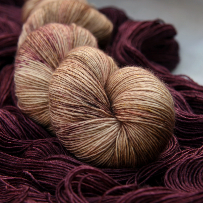 A skein of rich peachy pink yarn laying on an unwound skein of a rich red