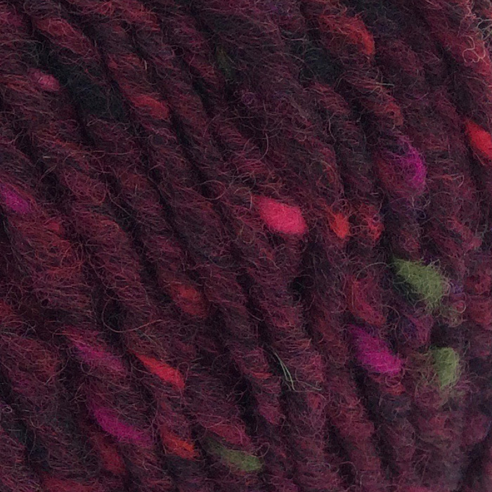 A deep rich burgundy yarn flecked with bright pinks and green in close up