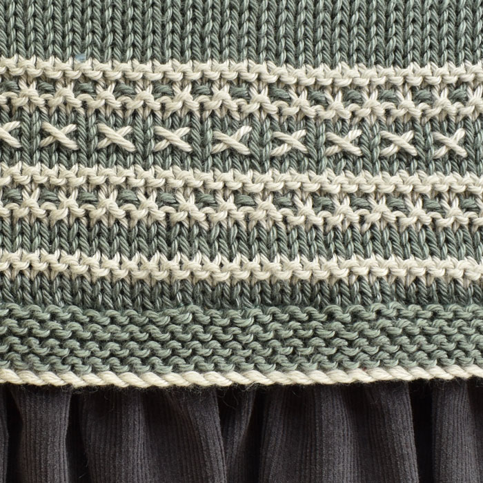 A close up of dress stitch detail in white on soft sage green