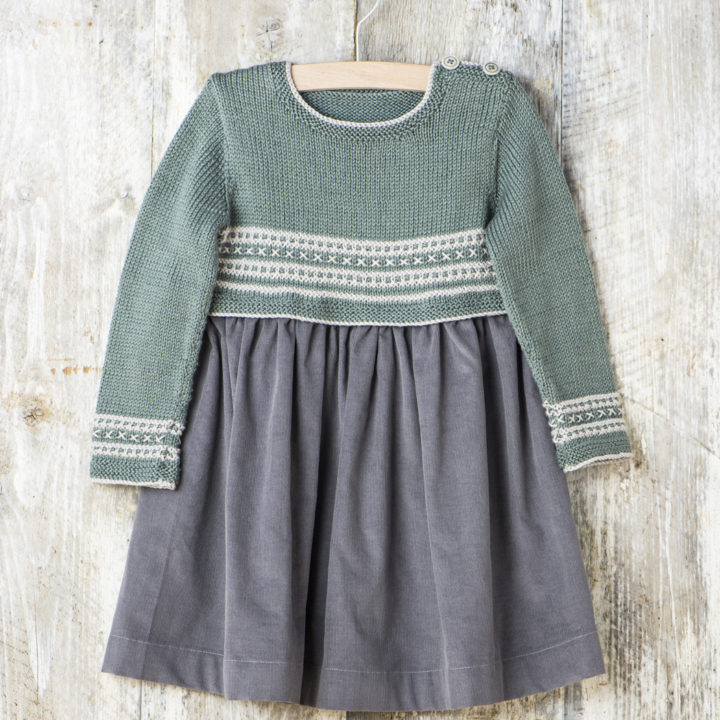 A child's dress on hanger against a wooden background. There're buttons at the shoulder of the knitted top and white stitch detail at the waist and cuffs with a light grey cord skirt