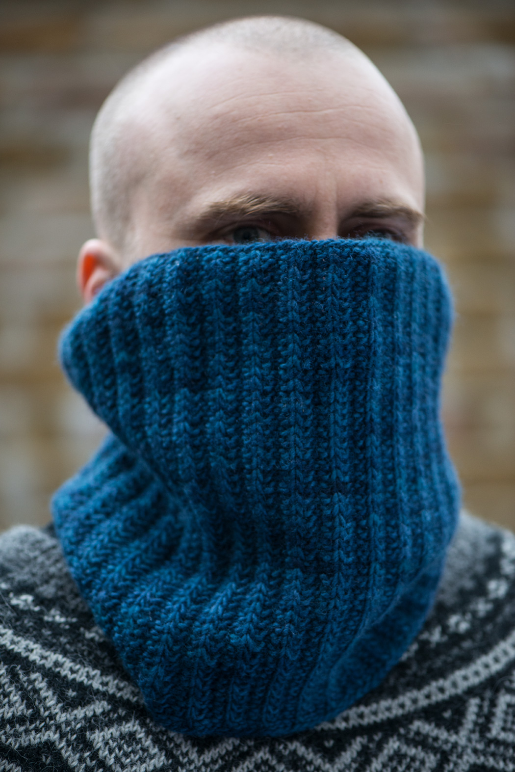 Man looking over the top of knitted cowl