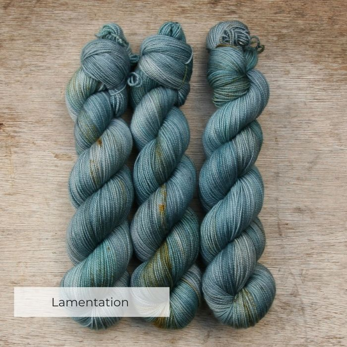 Three skeins of turquoise, blue and grey speckled with gold and brown