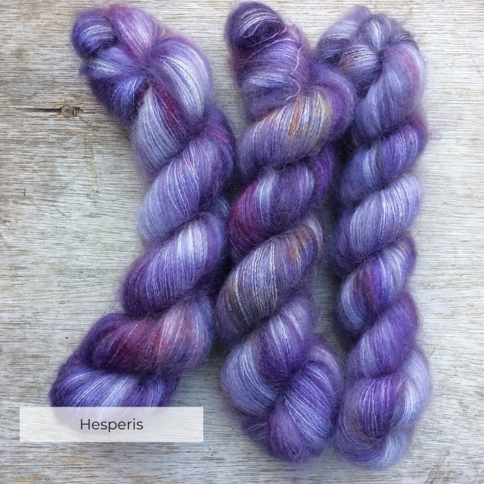 Three skeins of yarn dyed in shades of violet, grey and purple with splashes of pink and yellow