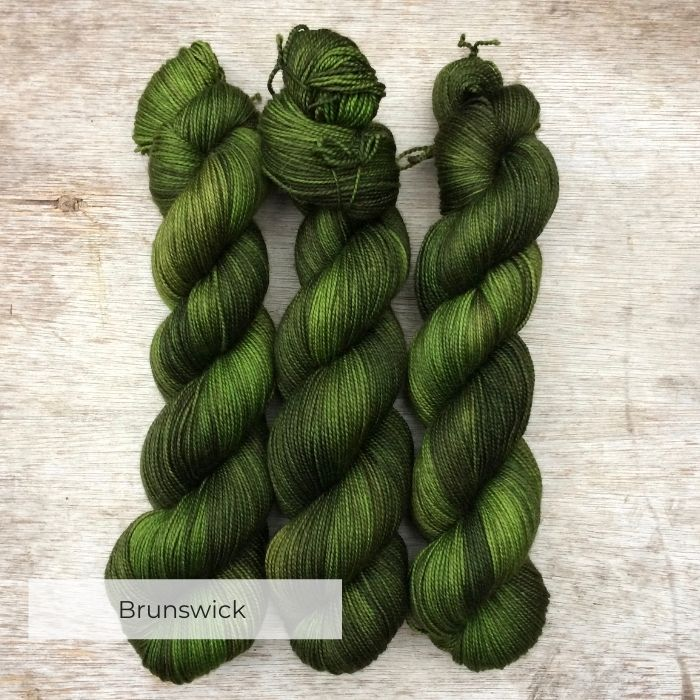 Three skeins of yarn in shades of green from forest to emerald