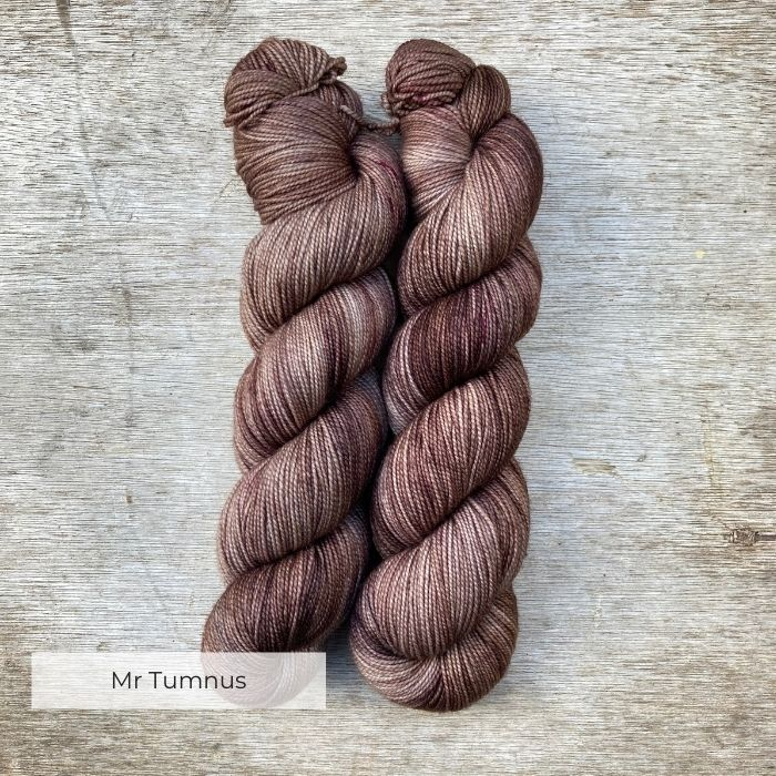 Two skeins of pink brown yarn speckled with deep burgundy