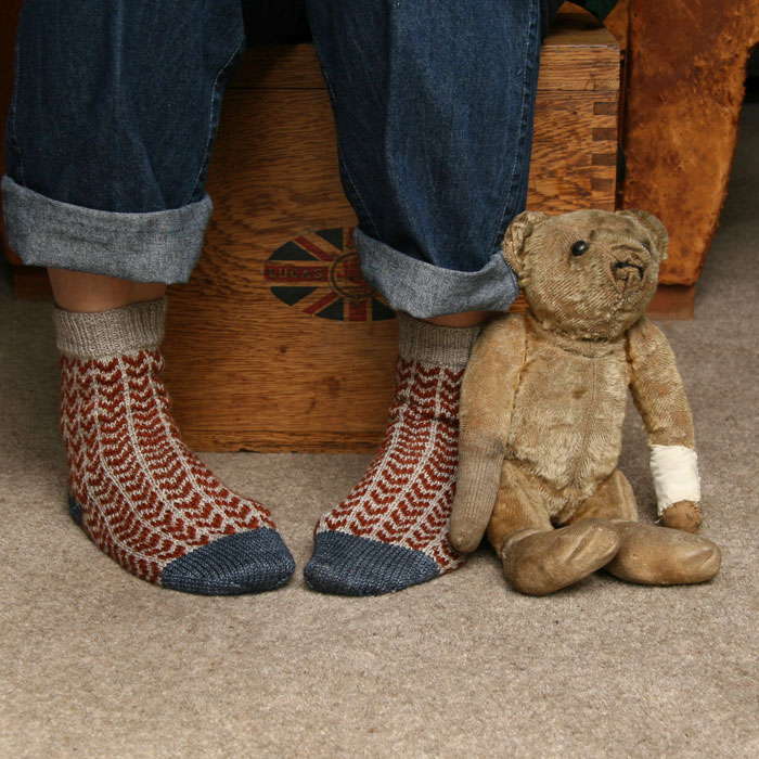 A woman sitting on an old wooden box with her jeans rolled up and a pair of splendid Zikzak socks on her turned in feet. A very vintage teddy bear is propped against her leg