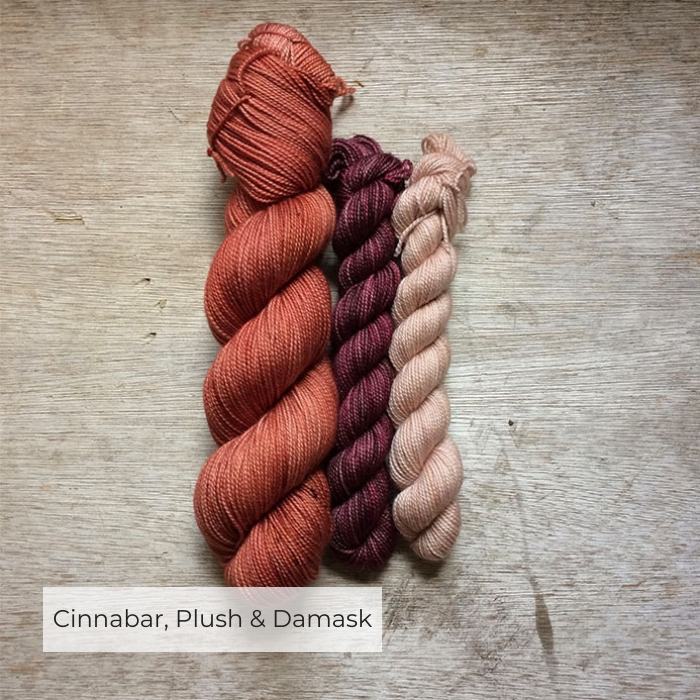 One full skein of yarn in a rich terracotta and two smaller skeins in a faded burgundy and soft peach pink