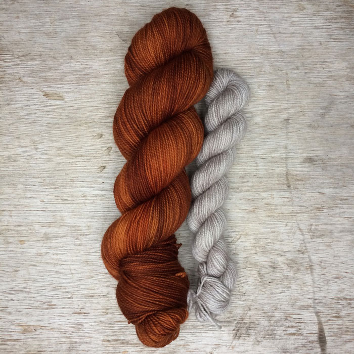 A large skein of ginger wool, a smaller skein of stone coloured