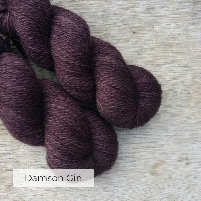 Two skeins of wool on a wood background. The yarn is the colour of a bottle of Damson Gin, purple but with brown too