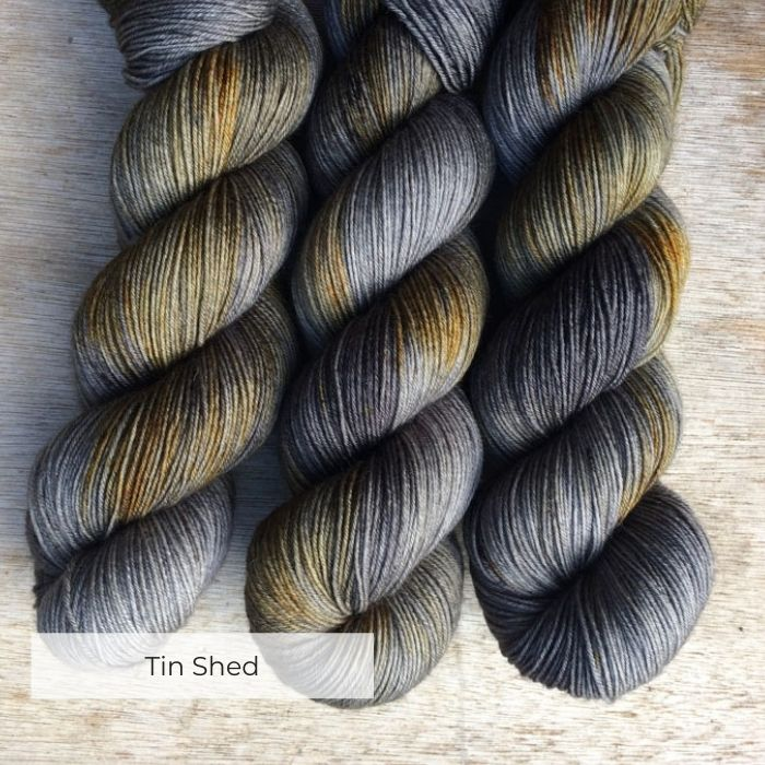 Three skeins of yarn in greys with splash of dark yellow