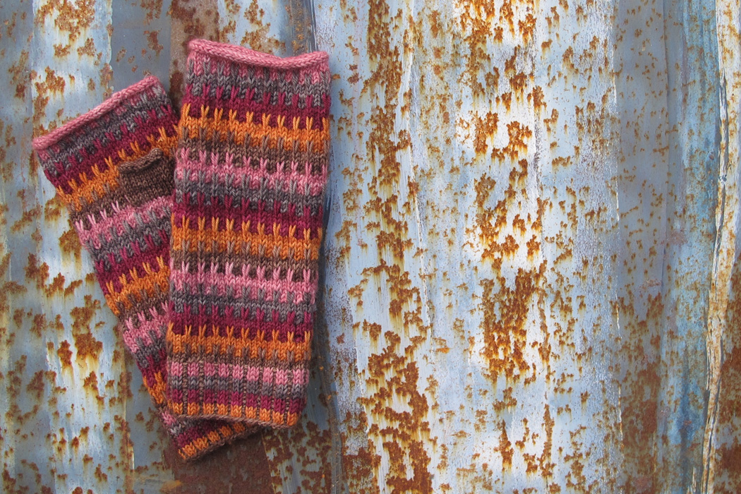A pair of Lewes mittens on a rusty metal background