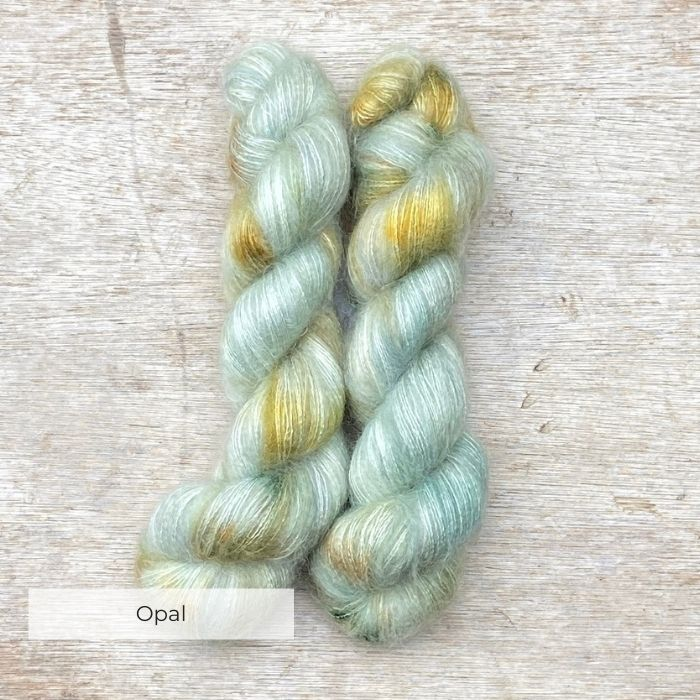 Two skeins of fluffy mohair in pale mint with gold splashes