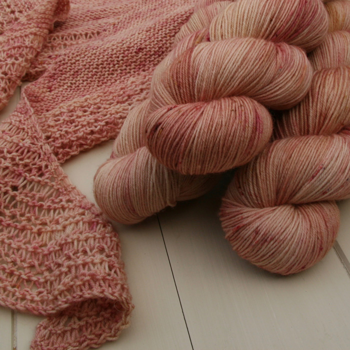 Three skeins of pink yarn and the edge of a shawl