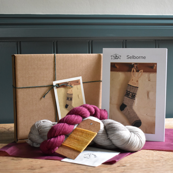 Kit contents: two skeins of our Classic Sock yarn in rose pink and stone laying on pink tissue paper in front of a cardboard box and printed pattern