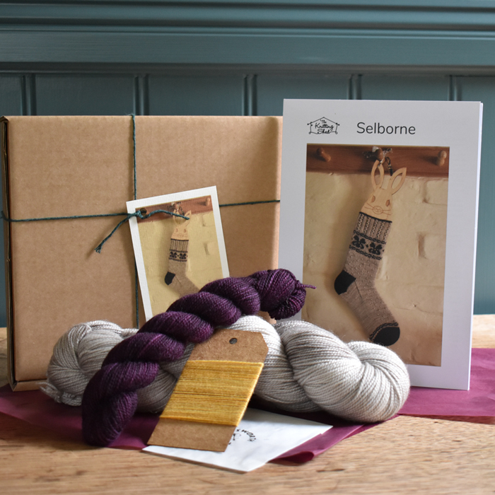 Kit contents: two skeins of our Classic Sock yarn in deep purple and stone laying on pink tissue paper in front of a cardboard box and printed pattern