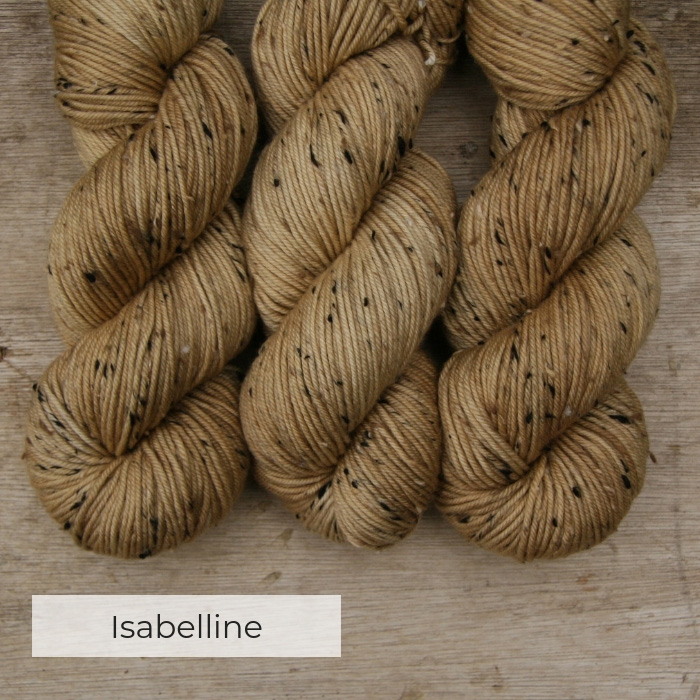 three skeins of hand dyed light gold yarn with black, white and brown neps