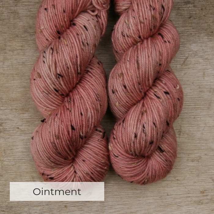 two skeins of hand dyed pink yarn with black, white and brown neps
