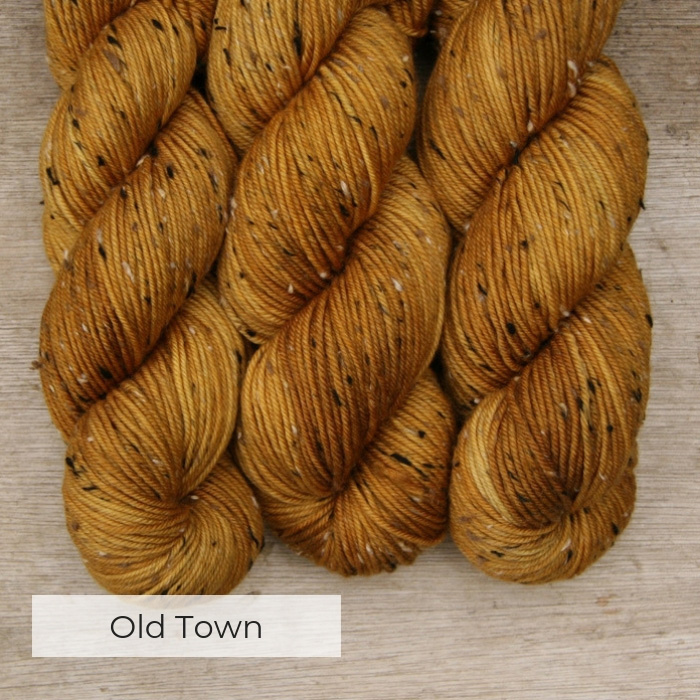 three skeins of hand dyed yellow yarn with black, white and brown neps
