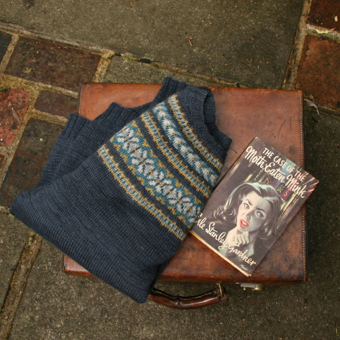 An old leather suitcase lays on a stone and brick floor with a beautiful colour work yoked jumper and vintage book on top