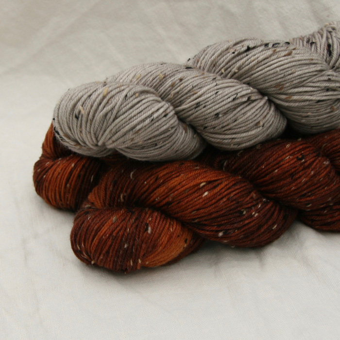 Three skeins of DK yarn in russet and stone