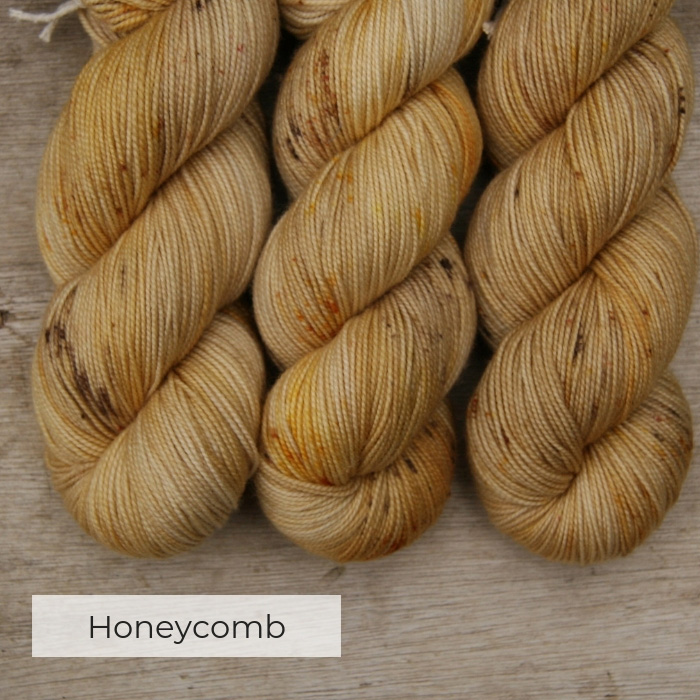 three skeins of semi solid yellow yarn with speckles of gold and brown