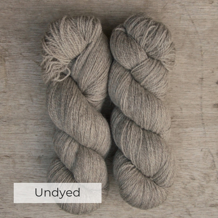 Two heathered skeins of yarn spun with of white and brown wool