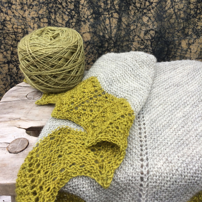 A grey shawl with acid green lace edging draped over a stool with a wound ball of paler greyer yarn