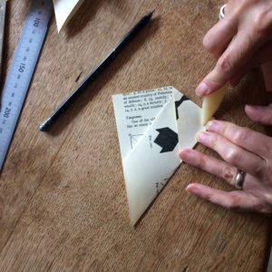Pair of hands using a bone folder to fold an envelope on a wooden table