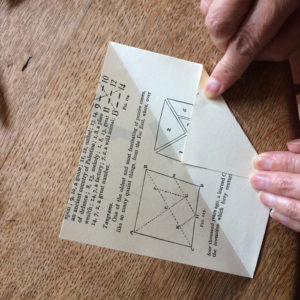 A pair of hands folding one corner of a square of paper up to the halfway line. The background is a wooden table
