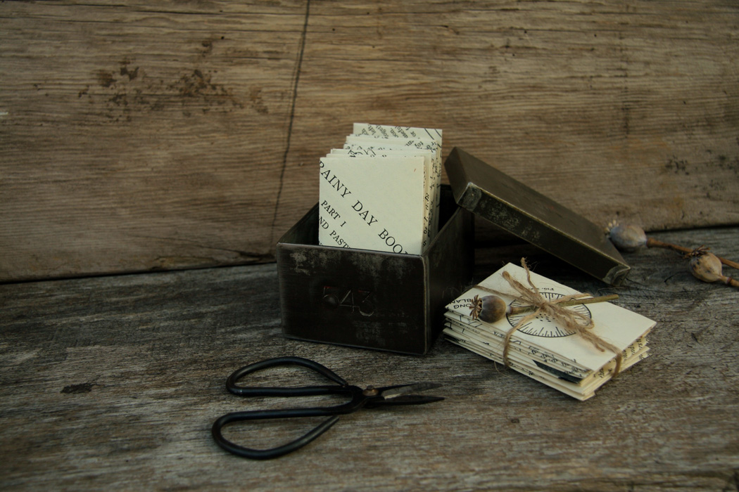 A tin box filled with hand made paper envelopes, the lid of the box leans against it and in front are a pair of scissors. To one side is a pile of envelopes tied with string and decorated with a poppy seed head.