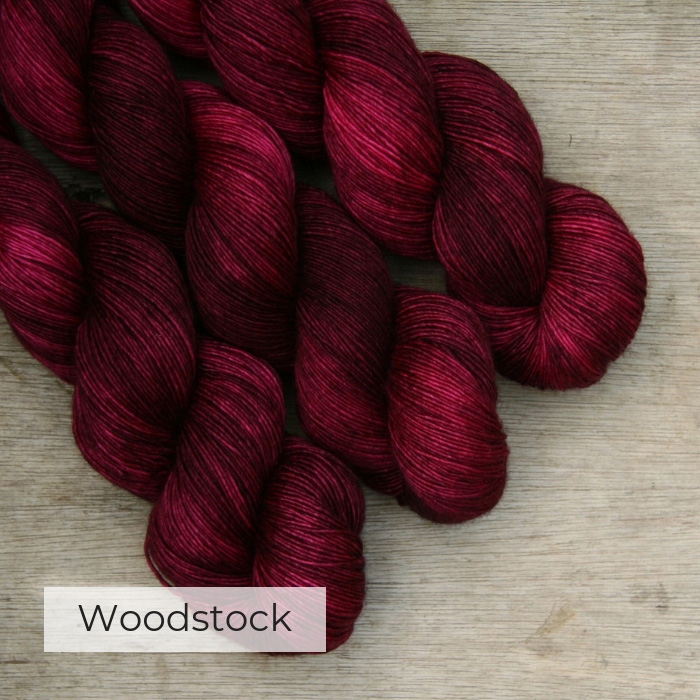three skeins of very dark pink yarn with a brighter pink coming through, on a wooden background