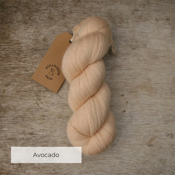 A single skein of soft peach yarn with a brown tie tag