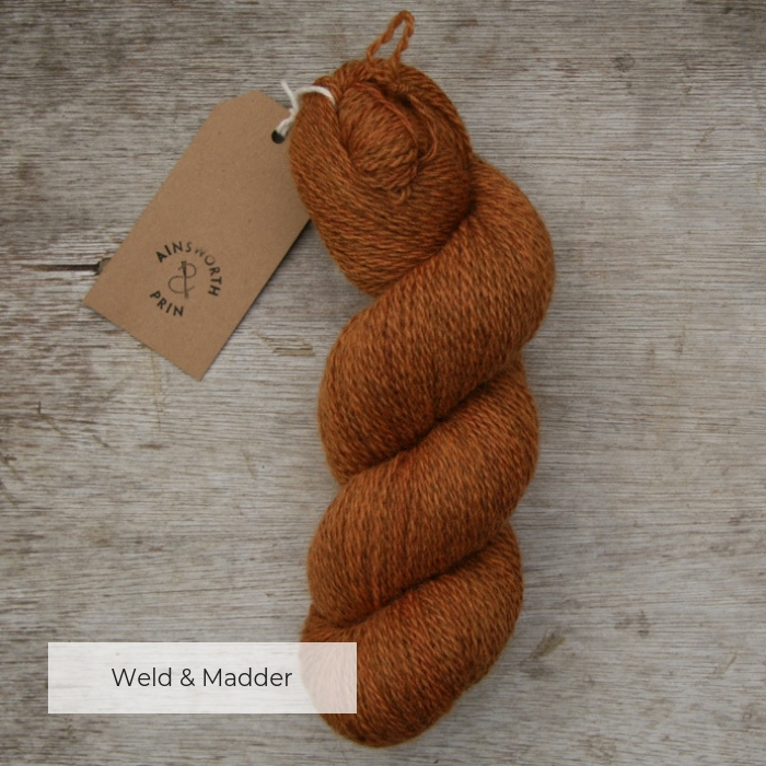 A single skein of russet orange yarn where the flecks of natural brown show through with a brown tie tag