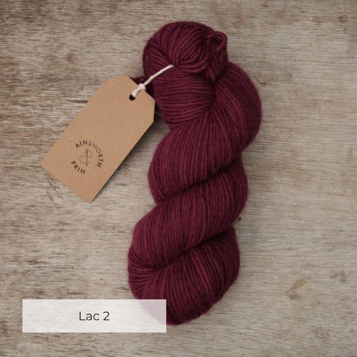 A single skein of rich red purple yarn with a brown tie tag