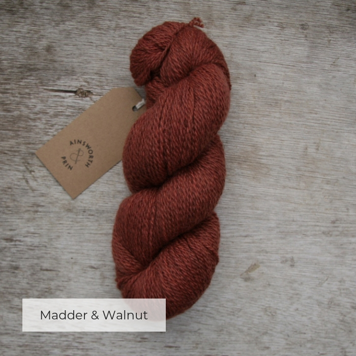 A single skein of warm orange brown yarn with a brown tie tag